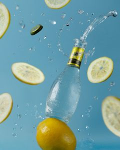 Flavored water in glass bottle with lemons